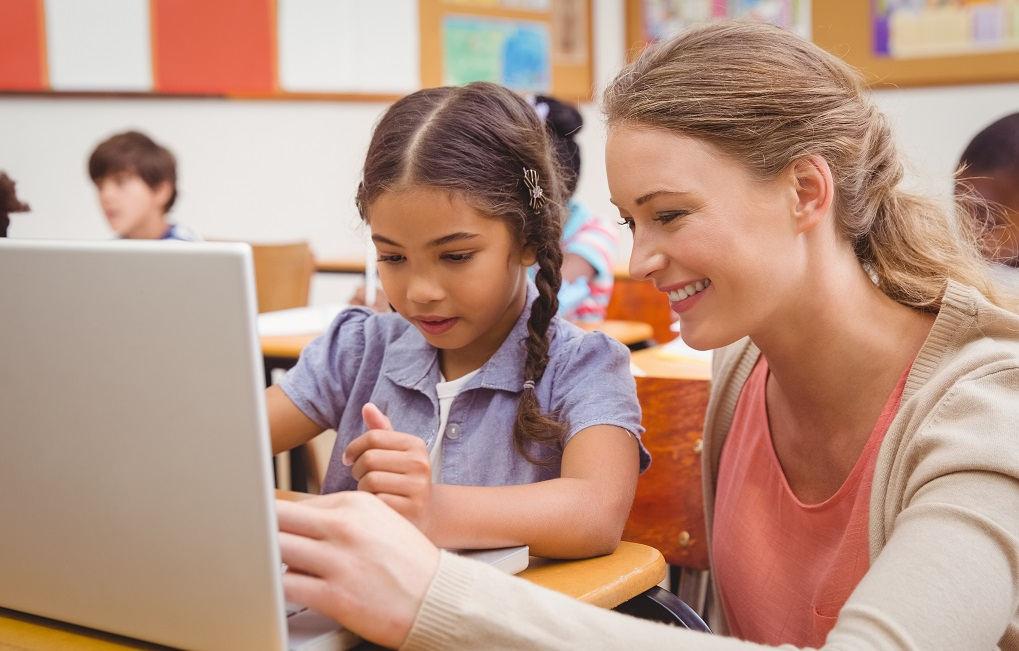 teacher helping student on laptop