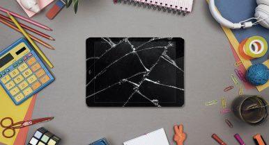 broken ipad overhead with school supplies
