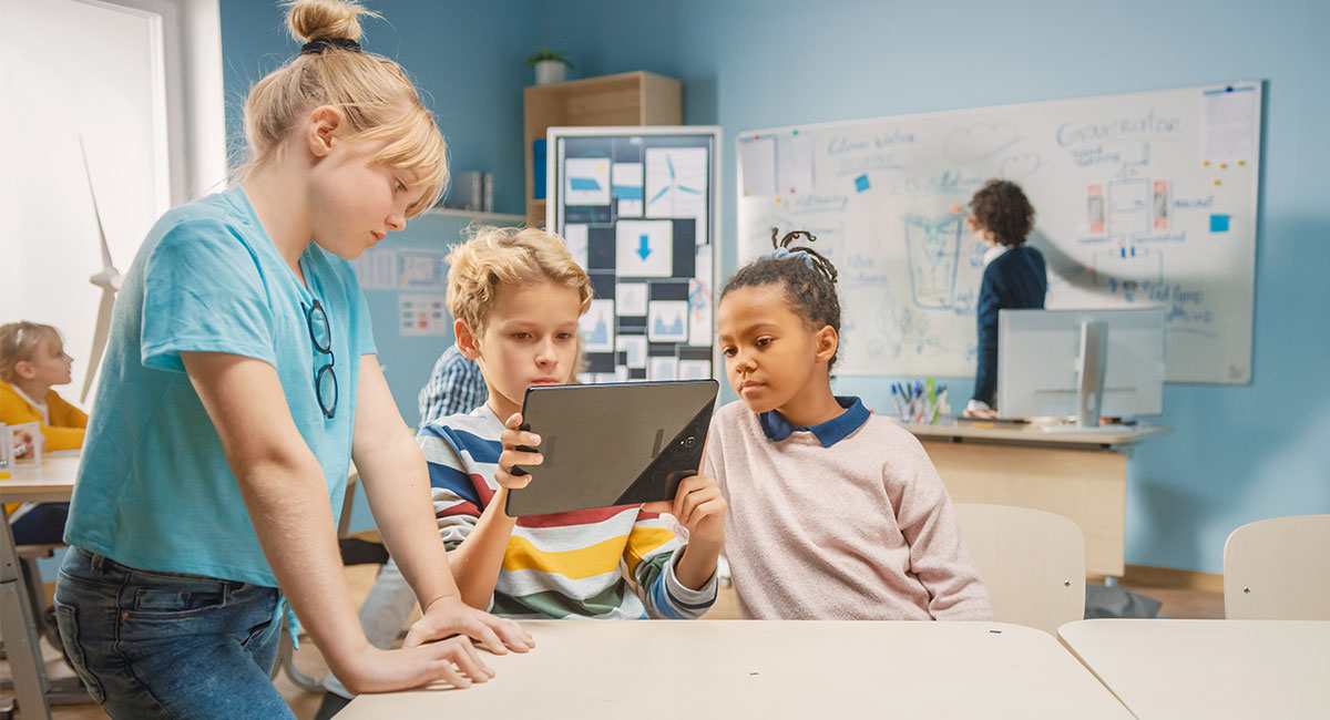 students within a classroom using tablet